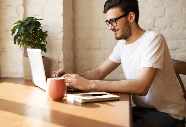 Młody brodaty dziennikarz w okularach pisze nowy artykuł w internecie i odpowiada na pytania swoich czytelników
