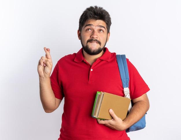 Młody brodaty facet student w czerwonej koszulce polo z plecakiem trzymając notebooki co życzenia skrzyżować palce z nadzieją wyrazem stojącym na białym tle