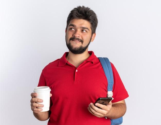 Młody brodaty facet student w czerwonej koszulce polo z plecakiem, trzymając smartfon i filiżankę kawy, patrząc na bok z chytrym uśmiechem na twarzy stojącej nad białą ścianą