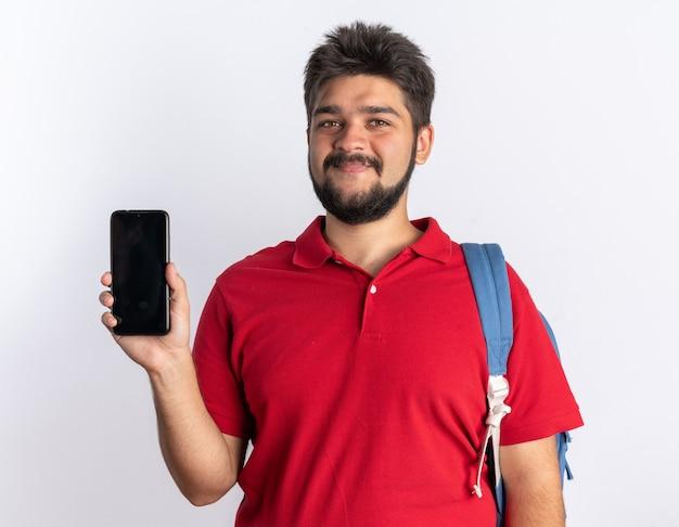 Młody, brodaty facet student w czerwonej koszulce polo z plecakiem, trzymając smartfon, patrząc na stojąco