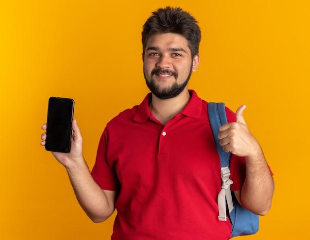 Młody, brodaty facet student w czerwonej koszulce polo z plecakiem, trzymając smartfon, patrząc uśmiechnięty pewnie pokazując kciuk do góry stojący