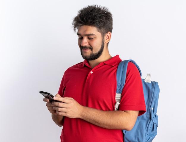Młody, brodaty facet student w czerwonej koszulce polo z plecakiem, trzymający smartfona, piszący wiadomości, uśmiechnięty pewnie, stojąc nad białą ścianą