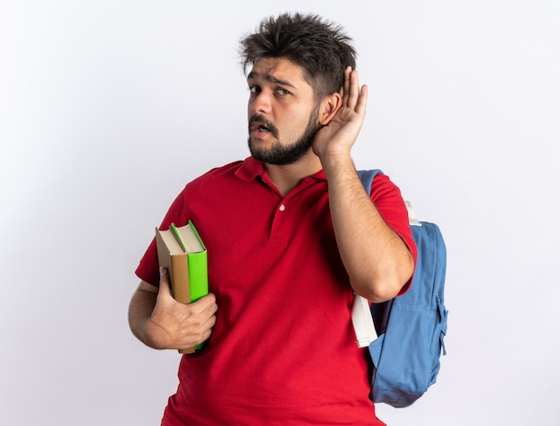 Młody, brodaty facet student w czerwonej koszulce polo z plecakiem trzymający zeszyty, próbujący słuchać ręką na uchu stojącym