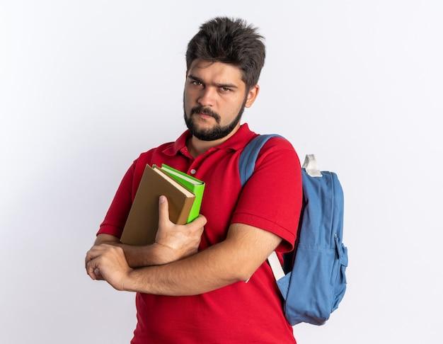 Młody, brodaty facet student w czerwonej koszulce polo z plecakiem, trzymający zeszyty z marszczącą twarz, stojący nad białą ścianą