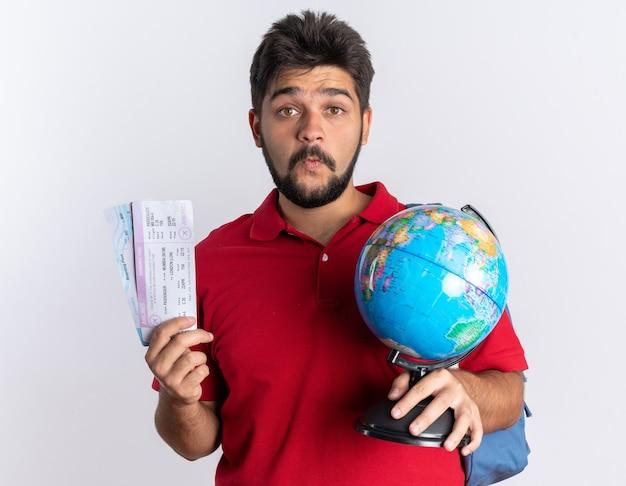 Młody, brodaty facet student w czerwonej koszulce polo z plecakiem trzymającym bilety lotnicze i kulą ziemską zaskoczony stojąc nad białą ścianą