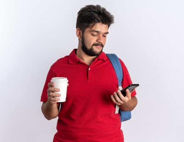 Młody, brodaty facet student w czerwonej koszulce polo z plecakiem trzymającym smartfona i filiżankę kawy, wyglądający pewnie uśmiechnięty, stojąc nad białą ścianą