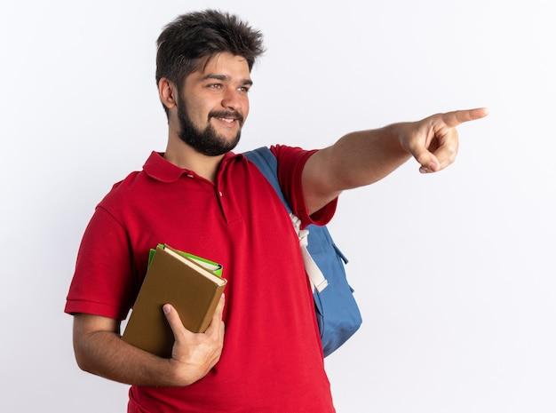 Młody brodaty facet student w czerwonej koszulce polo z plecakiem trzymającym zeszyty, patrząc na bok, uśmiechając się radośnie wskazując palcem wskazującym na coś stojącego nad białą ścianą