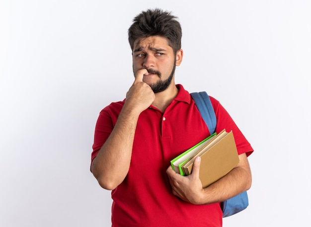 Młody brodaty facet student w czerwonej koszulce polo z plecakiem trzymającym zeszyty, patrząc na bok zestresowane i nerwowe obgryzające paznokcie stojące nad białą ścianą