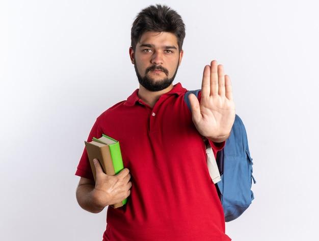 Młody brodaty facet student w czerwonej koszulce polo z plecakiem trzymającym zeszyty z poważną twarzą wykonującą gest zatrzymania ręką stojącą nad białą ścianą