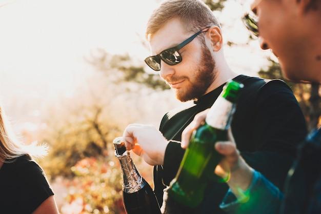 Młody brodaty facet w okularach przeciwsłonecznych otwierając butelkę szampana podczas świętowania z przyjaciółmi na wsi