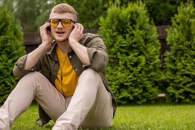 Młody brodaty facet w żółtych okularach niedbale ubrany siedzi na trawie, słuchając muzyki w słuchawkach i radośnie śpiewa z zamkniętymi oczami na zielonym tle. skopiuj miejsce