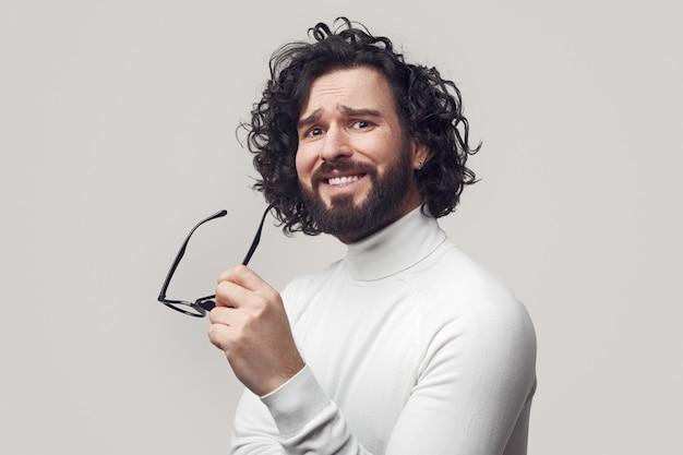 Młody brodaty facet z kręconymi włosami w okularach w ręku, patrząc na kamerę ze zdziwionym spojrzeniem i wątpliwościami na szarym tle