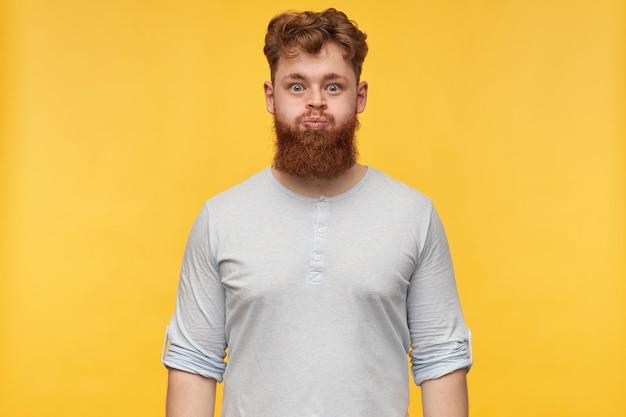 Młody brodaty facet ze stylową fryzurą i szeroko otwartymi oczami nadyma się na żółto.
