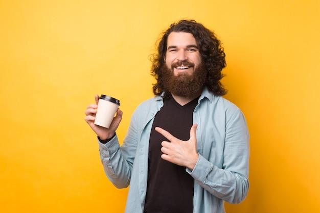 Młody brodaty hipster mężczyzna z długimi włosami, wskazując na papierową filiżankę kawy na żółtym tle