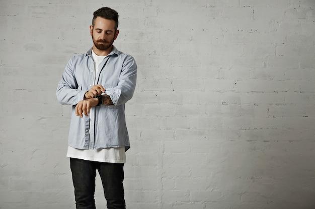 Młody brodaty hipster podwija rękaw swojej nieformalnej jasnej dżinsowej koszuli z tatuażami na ramieniu i białymi ceglanymi ścianami
