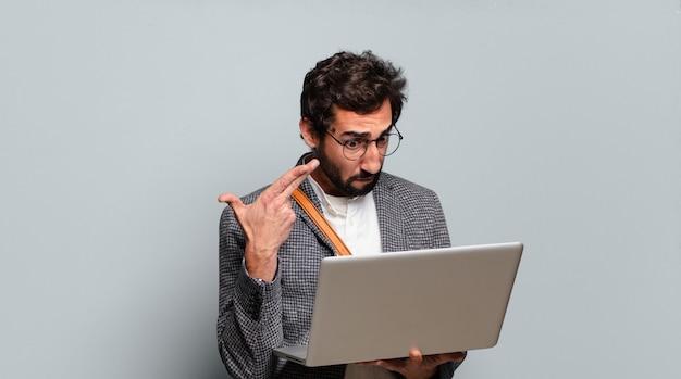 Młody brodaty i szalony biznesmen z laptopem