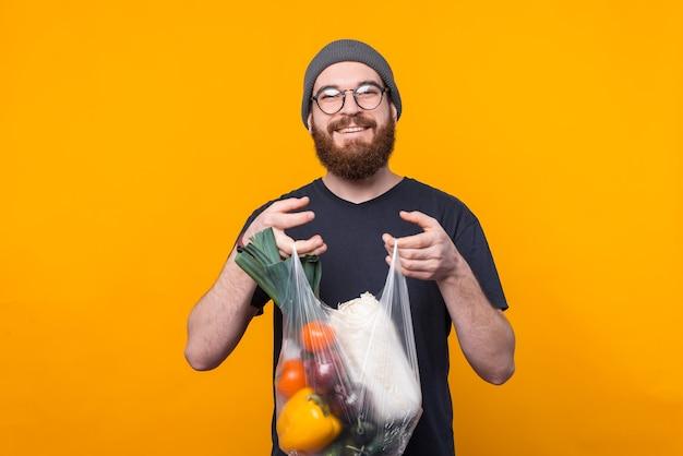 Młody, brodaty i wesoły mężczyzna patrzy uśmiechem i trzyma sakiewkę z artykułami spożywczymi