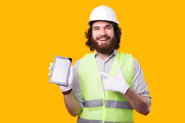 Młody, brodaty inżynier, uśmiechając się do kamery, pokazuje nowy tablet w pobliżu żółtej ściany