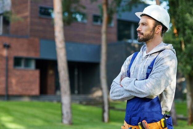 Młody, brodaty inżynier w kasku, odwracający wzrok, pozujący na zewnątrz podczas pracy przy budowie domku