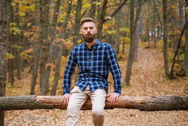 Młody brodaty kaukaski mężczyzna w kraciastej koszuli podróżuje samotnie po jesiennym lesie i spogląda na bo...