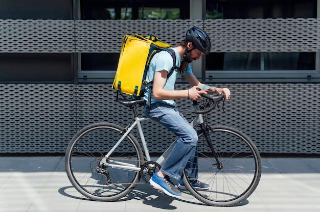Młody brodaty kurier dostarczający jedzenie na rowerze, sprawdzający zamówienie za pomocą smartfona. koncepcja usługi dostawy