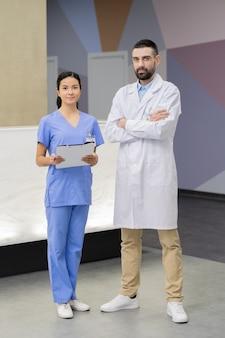 Młody brodaty lekarz w białym fartuchu skrzyżował ramiona przy klatce piersiowej, stojąc przy swoim asystencie z touchpadem na tle recepcji