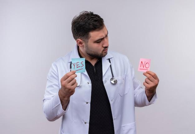 Młody brodaty lekarz w białym fartuchu ze stetoskopem trzymający papiery przypominające ze słowami tak i nie patrząc na nich zaintrygowany