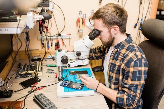Młody brodaty mechanik siedzi przy stole przed mikroskopem, aby zobaczyć drobne szczegóły zepsutych gadżetów w warsztacie