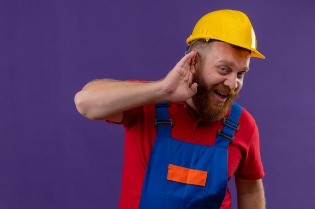 Młody brodaty mężczyzna budowniczy w mundurze budowlanym i hełmie ochronnym, trzymając rękę w pobliżu ucha, próbując słuchać rozmowy kogoś na fioletowym tle
