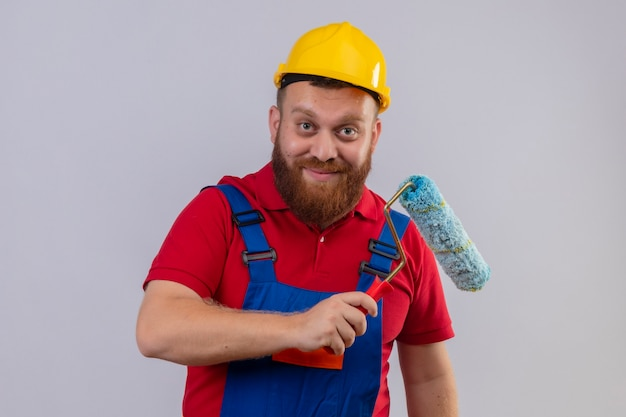 Młody brodaty mężczyzna budowniczy w mundurze budowlanym i kasku ochronnym, trzymając wałek do malowania patrząc na kamery szczęśliwy i pozytywnie uśmiechnięty 2