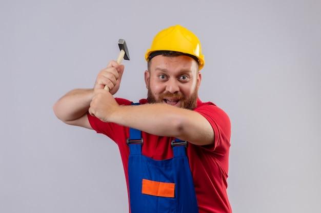 Młody brodaty mężczyzna budowniczy w mundurze budowy i hełm ochronny kołysząc młotkiem patrząc na kamery z uśmiechem