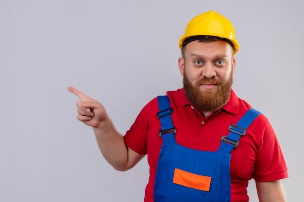 Młody brodaty mężczyzna budowniczy w mundurze budowy i hełmie ochronnym patrząc na kamery, wskazując palcem na bok z poważną miną