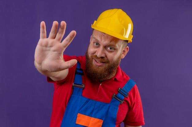 Młody brodaty mężczyzna budowniczy w mundurze budowy i hełmie ochronnym, patrząc przestraszony z otwartą ręką, robiąc znak stopu na fioletowym tle