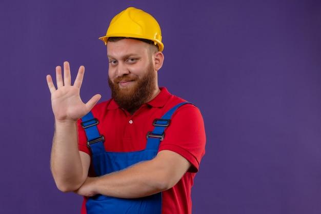Młody brodaty mężczyzna budowniczy w mundurze budowy i hełmie ochronnym, uśmiechając się, pokazując i wskazując palcami numer pięć na fioletowym tle