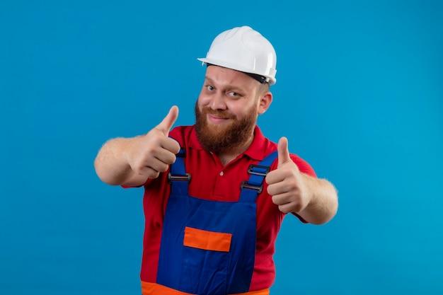 Młody brodaty mężczyzna budowniczy w mundurze budowy i hełmie ochronnym uśmiechnięty przyjazny pokazując kciuki obiema rękami