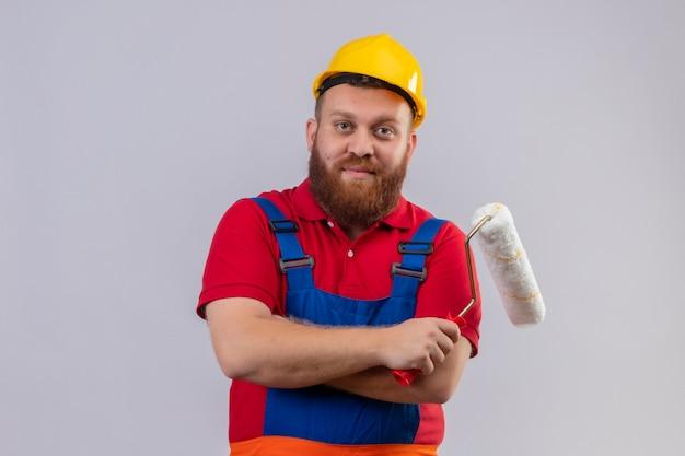 Młody brodaty mężczyzna budowniczy w mundurze budowy i kasku ochronnym, trzymając wałek do malowania patrząc na kamery z pewnym uśmiechem