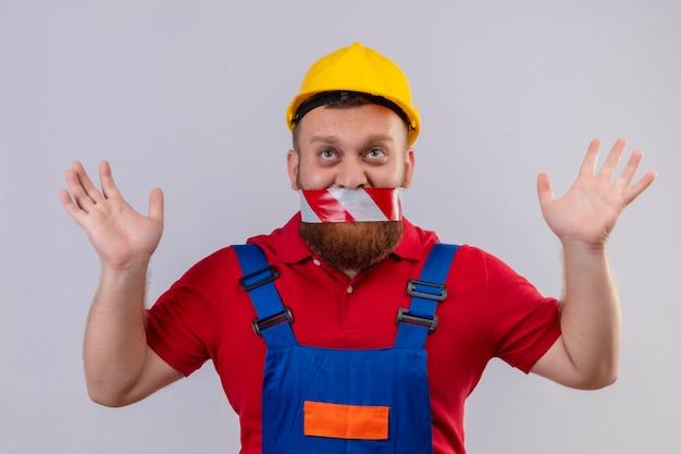 Młody brodaty mężczyzna budowniczy w mundurze konstrukcyjnym i kasku ochronnym z taśmą na ustach, patrząc w górę podnosząc ręce w sarrender