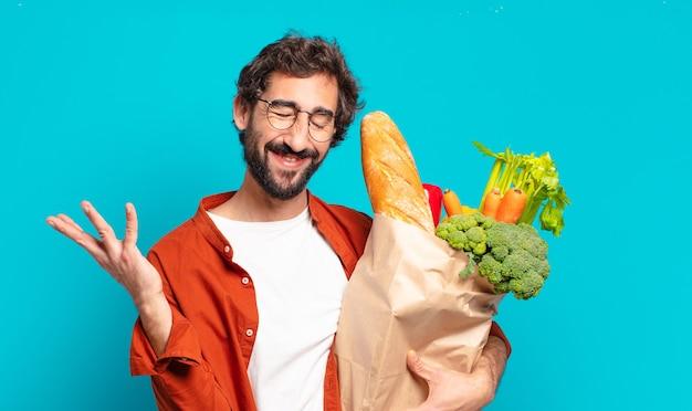 Młody brodaty mężczyzna czuje się szczęśliwy, zaskoczony i wesoły, uśmiecha się z pozytywnym nastawieniem, realizuje rozwiązanie lub pomysł i trzyma torbę z warzywami