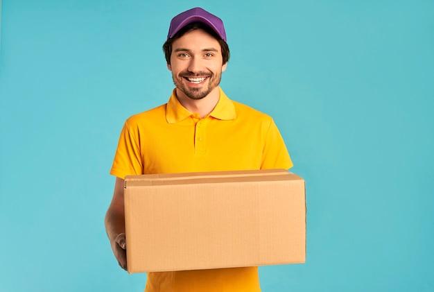 Młody brodaty mężczyzna dostawy kurier w mundurze posiada pudełko na białym tle. dostawa do domu.