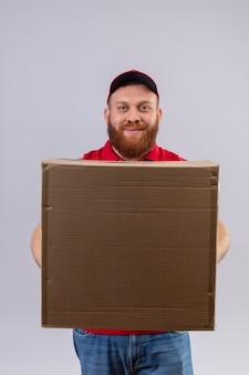 Młody brodaty mężczyzna dostawy w czerwonym mundurze i czapce trzyma karton patrząc na kamery z pewnym uśmiechem