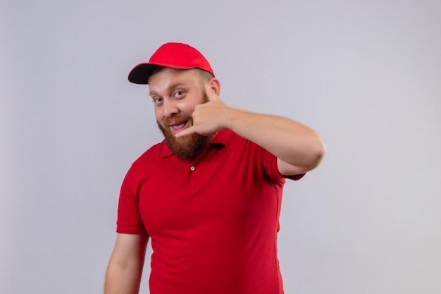 Młody brodaty mężczyzna dostawy w czerwonym mundurze i czapce uśmiechnięty, robiąc cal mnie gest ręką