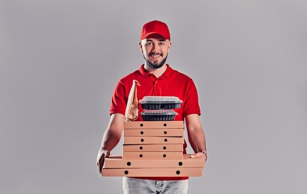 Młody brodaty mężczyzna dostawy w czerwonym mundurze z pudełka po pizzy, pudełka na lunch i papierową torbę na białym tle na szarym tle.