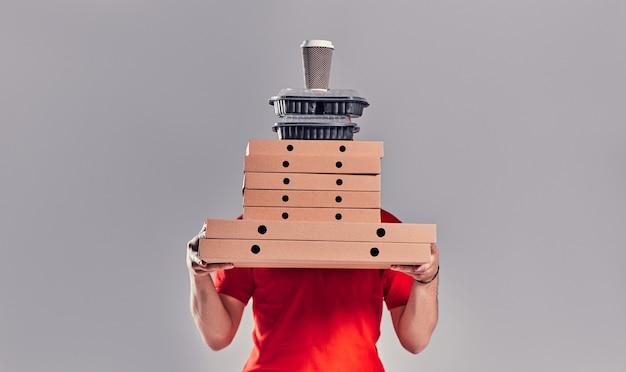Młody brodaty mężczyzna dostawy w czerwonym mundurze z pudełka po pizzy, pudełko na lunch i kawa na białym tle na szarym tle.
