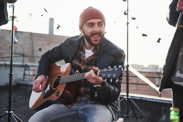 Młody brodaty mężczyzna. facet z gitarą akustyczną śpiewa. przyjaciele bawią się na imprezie na dachu z dekoracyjnymi kolorowymi żarówkami