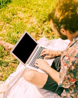 Młody brodaty mężczyzna gapi się przy laptopem w haliźnie