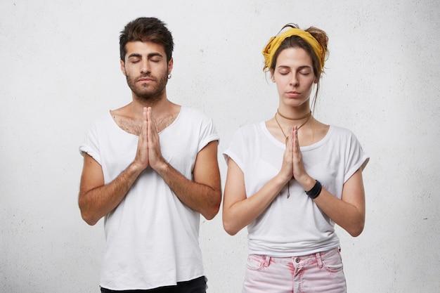 Młody brodaty mężczyzna i ładna kobieta medytują w pomieszczeniu, zamykając oczy i trzymając ręce razem, czując relaks