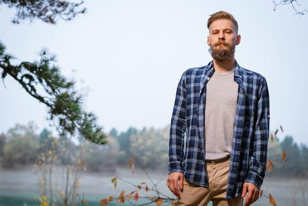 Młody brodaty mężczyzna kaukaski w kraciastej koszuli podróżujący samotnie w jesiennym lesie i patrzący w bok