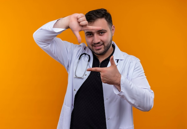 Młody brodaty mężczyzna lekarz ubrany w biały fartuch ze stetoskopem, co ramka z palcami patrząc przez tę ramkę uśmiechnięty