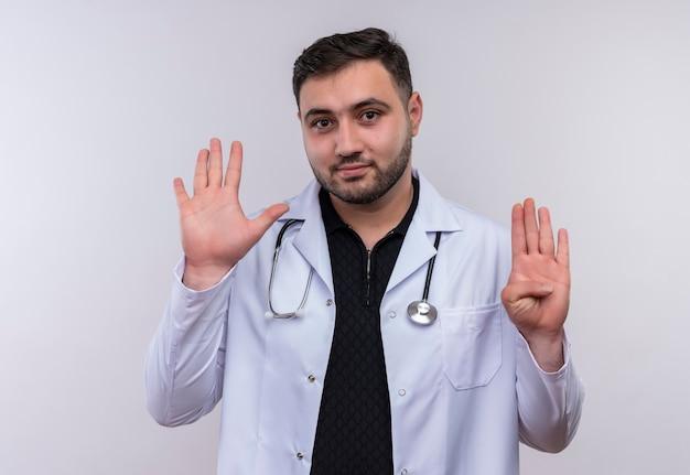 Młody brodaty mężczyzna lekarz ubrany w biały fartuch ze stetoskopem i skierowaną w górę palcami numer dziewięć uśmiechnięty pewnie