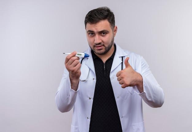 Młody brodaty mężczyzna lekarz ubrany w biały fartuch ze stetoskopem trzymając cyfrowy termometr uśmiechnięty pewnie pokazując kciuk do góry